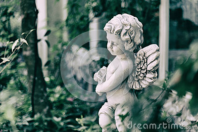 Beauty Cupid statue of Angel in vintage garden on summer. Holding bouquet flowers in his hand