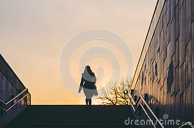 Silhouette of a woman emerging from an underpass. City life