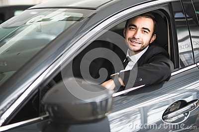 Happy smiling driver in the car, portrait of young successful business man