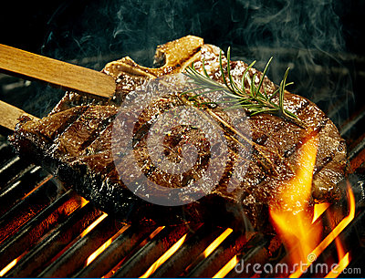 Spicy t-bone steak grilling over a summer barbecue