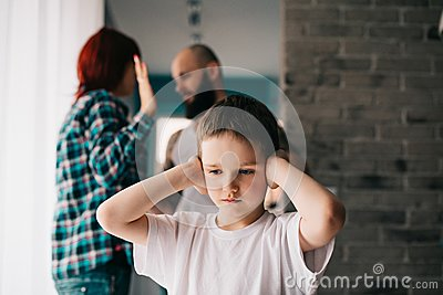 Sad child covering his ears with hands during parents quarrel.