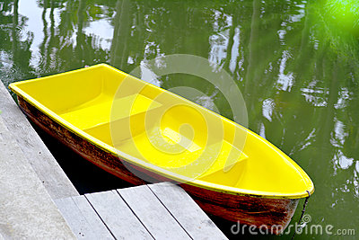 Yellow row boats in the lagoon or Yellow rowboat on water in lake with light of sunset