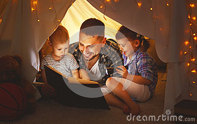 Happy family father and children reading a book  in  tent at hom
