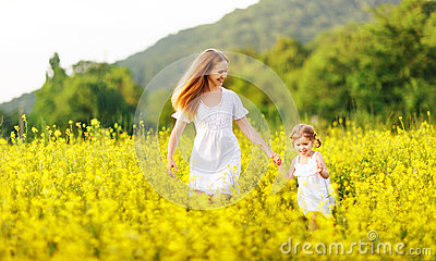 Happy family mother and child daughter running in nature in sum