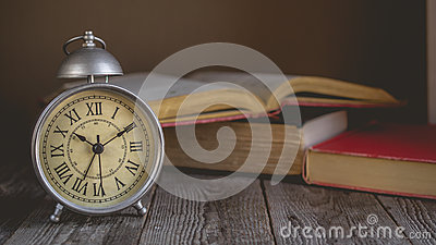 Roman Numeral in Vintage Alarm Clock and Open Book Background wi