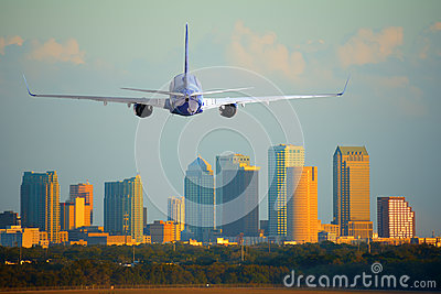 Passenger jet airliner plane arriving or departing Tampa International Airport in Florida at sunset or sunrise