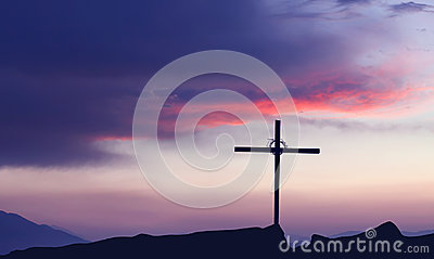Silhouette of Christian cross at sunrise or sunset concept of re