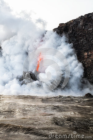 Lava flowing into ocean with steam and smoke