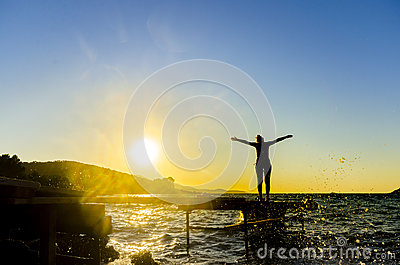 Portrait of healthy young hispanic woman standing on the beach pier with her hands outstretched against sunset