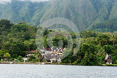 Several houses build at the foot of a mountain next to a lake in Sumatra Samosir Island.