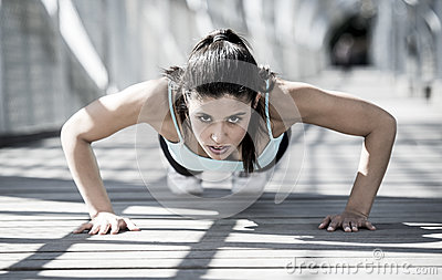 Athletic sport woman doing push up before running in urban training workout