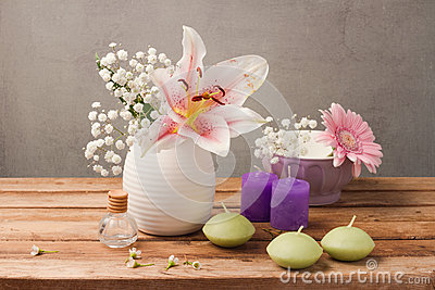 Spa and wellness concept with flowers in vase and candles on wooden table