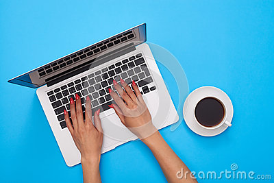 Hands of woman on a keyboard of the modern laptop over blue flat