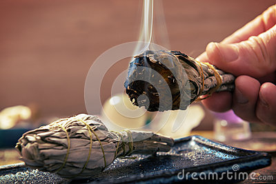 Man burning white sage incense