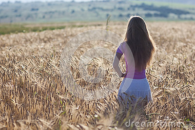 Happy young girl in golden wheat field. Young woman enjoying nat