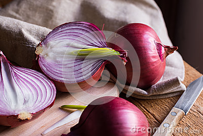 Red or purple onion cut in half, green germs, wood breadboard, linen towel, knife, kitchen table by window