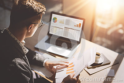 Young finance market analyst in eyeglasses working at sunny office on laptop while sitting at wooden table.Businessman