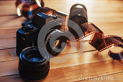 Old photo film and analog camera on table. Roll of photographic . Beautiful vintage design.