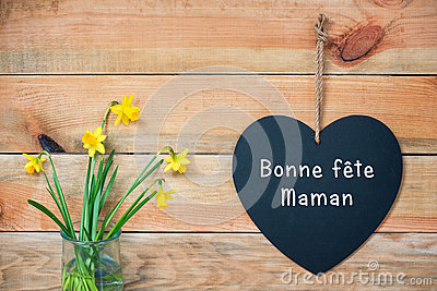 Bonne fete maman, French mothers day card, wood planks with daffodils and a blackboard in shape of a  heart