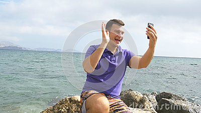 Young smiling man having a video call on smart phone at the sea beach. Happy guy making video online chats on beautiful