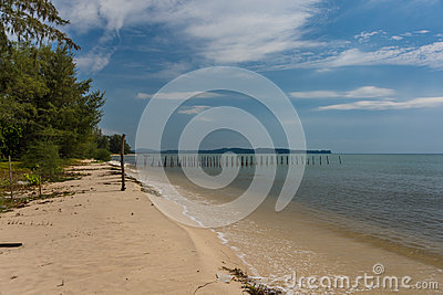 2 rows of wooden posts go out in to a calm paradise sea off of a
