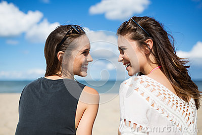Two beautiful women on beach looking at each other laughing