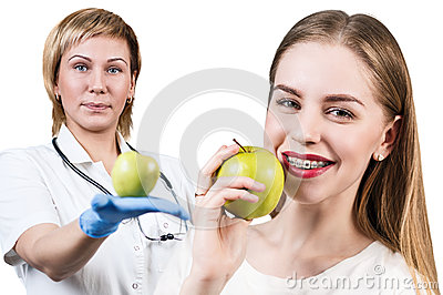 Dentist giving apple fruit to young woman.