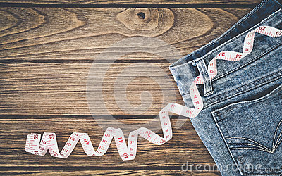 Weight loss concept, Blue jeans and measuring tape on wooden bac