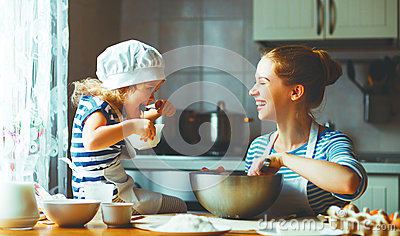 Happy family in kitchen. mother and child preparing dough, bake