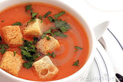 Tomato soup with croutons in bowl on white