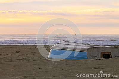 Row boat upside down on a winter shore at sunset