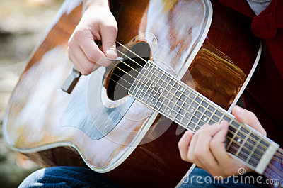 Hands strumming guitar