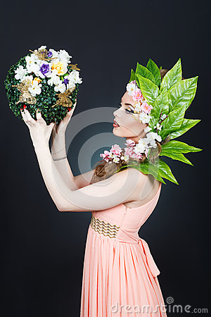 Beauty Spring girl with flowers hair. Beautiful model woman with flowers on her head. The Nature Of Hairstyle. Summer