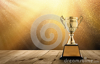 champion golden trophy on wood table with copy space and gold Tw