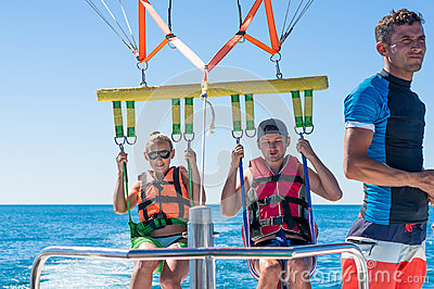Happy couple Parasailing in Dominicana beach in summer. Couple under parachute hanging mid air. Having fun. Tropical Paradise. Pos