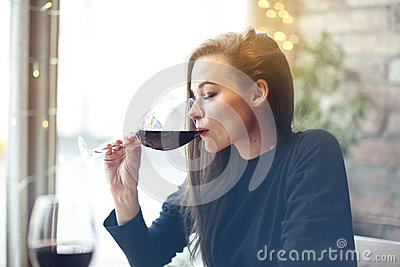Beautiful young woman drinking red wine with friends in cafe, portrait with wine glass near window. Vocation holidays evening conc