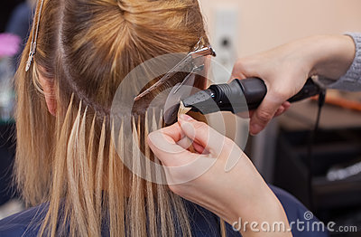 The hairdresser does hair extensions to a young girl, a blonde in a beauty salon.