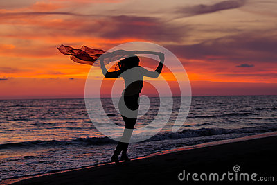 Silhouette of young girl, jumping with silk cloth against of sea sunset