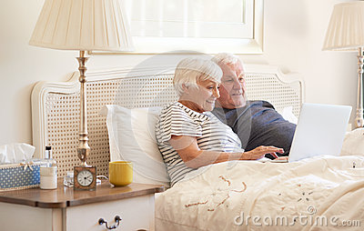 Seniors using a laptop on their bed in the morning