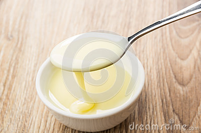 Spoon with sweet condensed milk above glass bowl