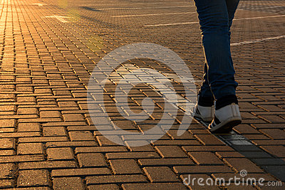 Forward movement. Feet on the road with arrows in the rays of the setting sun