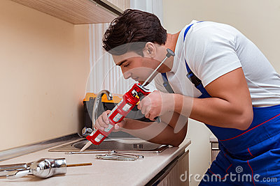 The young repairman working at the kitchen