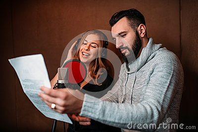 Music producer and female singer in headphones