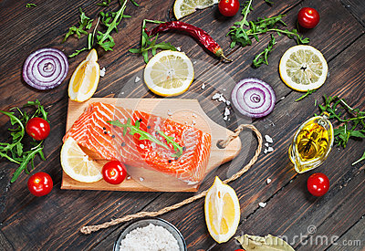 Delicious portion of fresh salmon fillet with aromatic herbs, spices and vegetables - healthy food, diet or cooking concept.