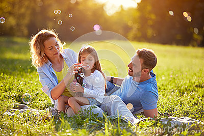 Child blow soup foam and make bubbles in nature