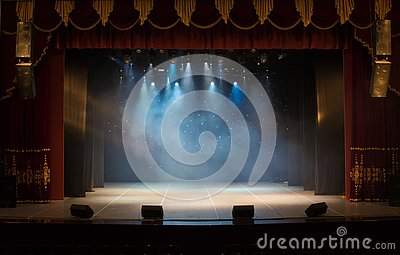 An empty stage of the theater, lit by spotlights and smoke