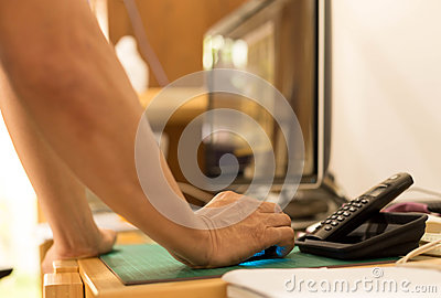 Man hand holding computer mouse with computer screen in the back