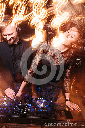 Clubbing, party, girl dancing with DJ at console