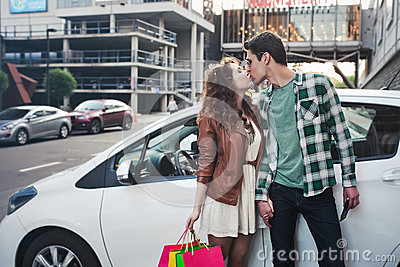 Beautiful young couple kisses near a car, makes a shopping