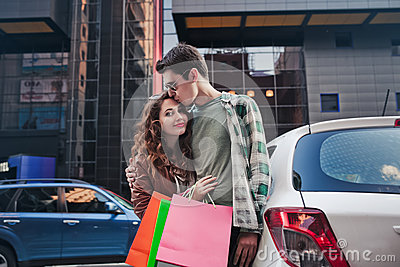 Beautiful young couple stands and kisses near a car, makes a shopping